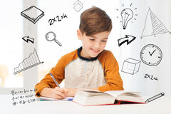 Smiling student boy writing to notebook at home Stock Photos