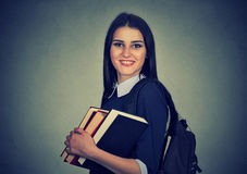 Smiling student carrying backpack and holding stack of books stock photos