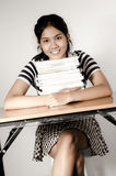Smiling student at desk. Smiling female student sitting at desk with pile of books wearing black and white dress Stock Photo