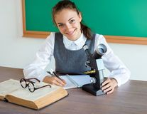 Smiling student doing research using microscope stock photos