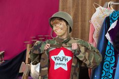 Smiling student dressed as army man. Smiling theater student dressed as army man holds jacket open Stock Photography