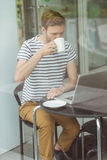 Smiling student drinking hot drink Royalty Free Stock Photography