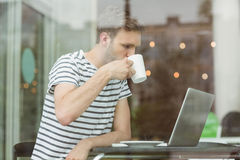 Smiling student drinking hot drink Stock Images