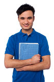 Smiling student embracing his note book. Cheerful college student holding notebook against white Royalty Free Stock Images
