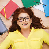 Smiling student in eyeglasses lying on floor Royalty Free Stock Photography