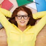 Smiling student in eyeglasses lying on floor Stock Image