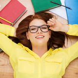 Smiling student in eyeglasses lying on floor Royalty Free Stock Photos