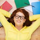 Smiling student in eyeglasses lying on floor Stock Photos