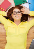 Smiling student in eyeglasses lying on floor Stock Photography