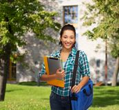 Smiling student with folders, tablet pc and bag Royalty Free Stock Images