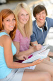 Smiling student friends sitting together studying Stock Photos