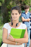 Smiling student girl. Closeup of student standing outside with handbook Stock Photo