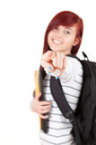 Smiling student girl with black backpack pointing Stock Image