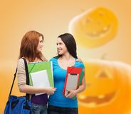 Smiling student girl with books and bag. Education, holidays, school, friendship and people concept - smiling student girls with books and bag over halloween Stock Photography