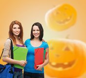 Smiling student girl with books and bag. Education, holidays, school, friendship and people concept - smiling student girls with books and bag over halloween Stock Image