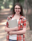 Smiling student girl with a clipboard on the background of the Park.  Royalty Free Stock Photo