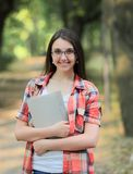 Smiling student girl with a clipboard on the background of the Park.  Stock Image