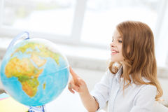 Smiling student girl with globe at school Stock Photo