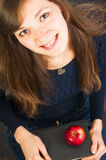 Smiling student girl holding books. Top view of a young smiling student girl holding books and apple Stock Photography