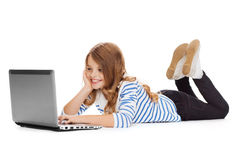Smiling student girl with laptop computer lying Royalty Free Stock Image