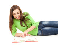 Smiling student girl lying down and reading book Royalty Free Stock Photos