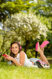 Smiling student girl lying in summer park Stock Photography