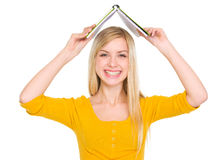 Smiling student girl making roof with book Stock Photography
