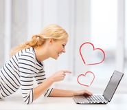 Smiling student girl pointing her finger at laptop. Love and internet concept - smiling student girl pointing her finger at laptop screen in college royalty free stock photos