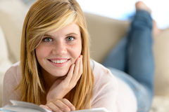 Smiling student girl read book lying sofa Stock Photography