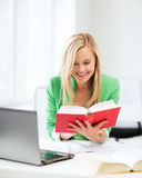 Smiling student girl reading book in college Stock Images