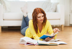 Smiling student girl reading books at home Royalty Free Stock Image