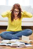 Smiling student girl reading books at home. Education and home concept - smiling student girl in eyeglasses reading books at home royalty free stock photo