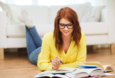 Smiling student girl reading books at home. Education and home concept - smiling student girl in eyeglasses reading books at home stock images