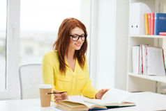 Smiling student girl reading books in library Stock Photo