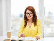 Smiling student girl reading books in library Royalty Free Stock Photo