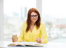 Smiling student girl reading books in library Royalty Free Stock Image