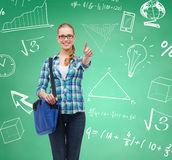 Smiling student girl showing thumbs up. Education, happiness and people concept - smiling student girl showing thumbs up over green board background royalty free stock photography