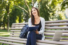 Smiling student girl sitting in park using laptop. Smiling student girl sitting on bench in park, working with laptop and taking notes, preparing for exams Royalty Free Stock Image