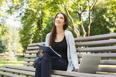 Smiling student girl sitting in park using laptop. Smiling student girl sitting on bench in park, working with laptop and taking notes, preparing for exams Stock Images