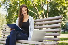 Smiling student girl sitting in park using laptop. Smiling student girl sitting on bench in park, working with laptop and taking notes, preparing for exams Stock Photo