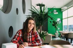Smiling student girl sitting at a table in a cafe looking to the side. In the pockets of her pen Royalty Free Stock Photos
