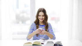 Smiling student girl with smartphone and books stock video footage