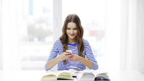 Smiling student girl with smartphone and books stock video