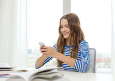 Smiling student girl with smartphone and books Royalty Free Stock Images
