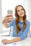 Smiling student girl with smartphone and books Royalty Free Stock Photos