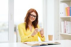 Smiling student girl with smartphone at school Stock Image
