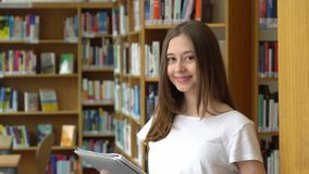 Happy teenage girl posing in the school library stock footage