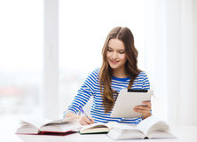 Smiling student girl with tablet pc and books Royalty Free Stock Photography