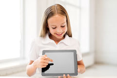 Smiling student girl with tablet pc computer. Education, technology and people concept - happy smiling student girl pointing finger to tablet pc computer screen Stock Images