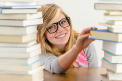 Smiling student girl take book from stack Stock Image